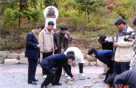 Fr. Thomas More Chung and others collecting rocks stained with Precious Blood